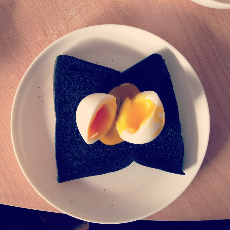 A market egg atop a slice of bamboo charcoal bread.