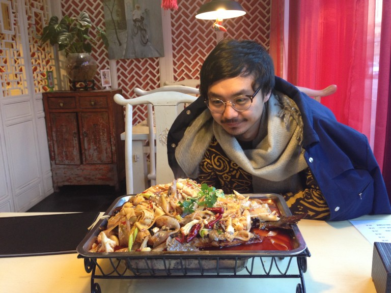 Chang eyes a giant catfish buried deep in a chewy pile of spicy glass noodles (made from sweet potato starch), vegetables and chillies.