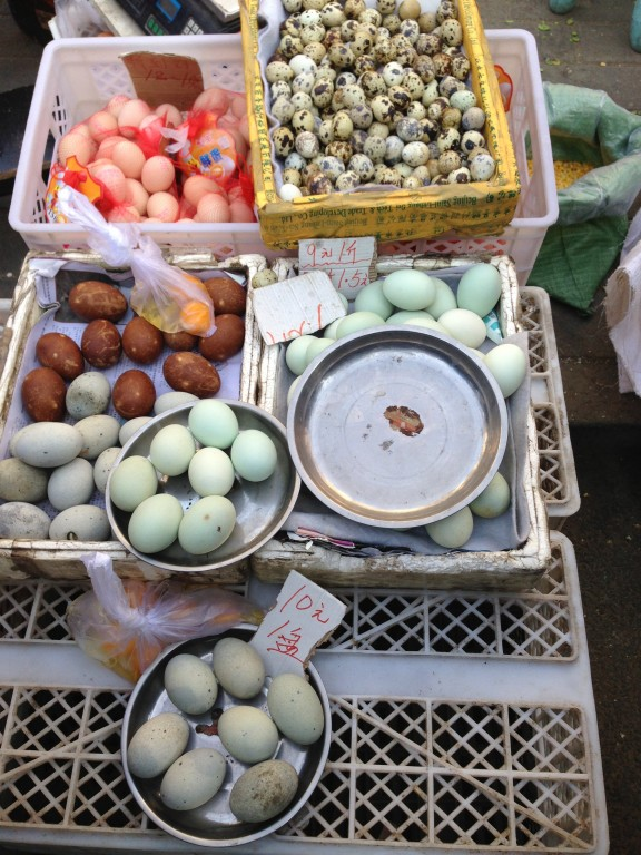 Eggs at the street market are bountiful and rich. Note the deep orange yolk on display next to the brown 100-year old eggs (preserved in a mixture of clay, ash, salt, quicklime and rice hulls for several weeks or months).