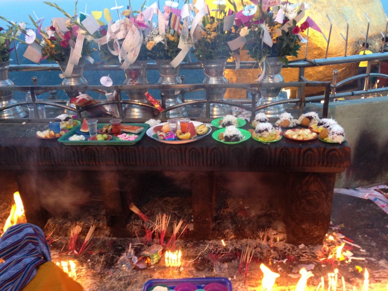 Offerings of all kinds--candles, incense, fruit, candy-- for the Buddha at Golden Rock.